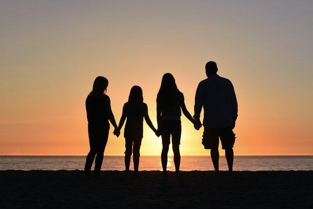 Familie vor Sonnenuntergang über dem Meer