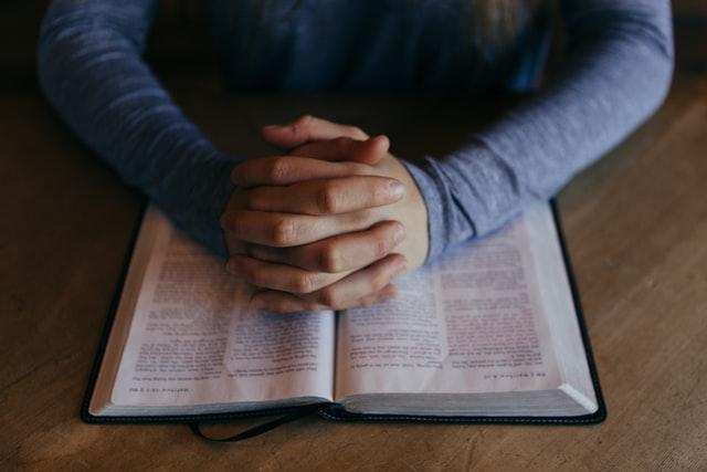 Gefaltete Hände über Buch